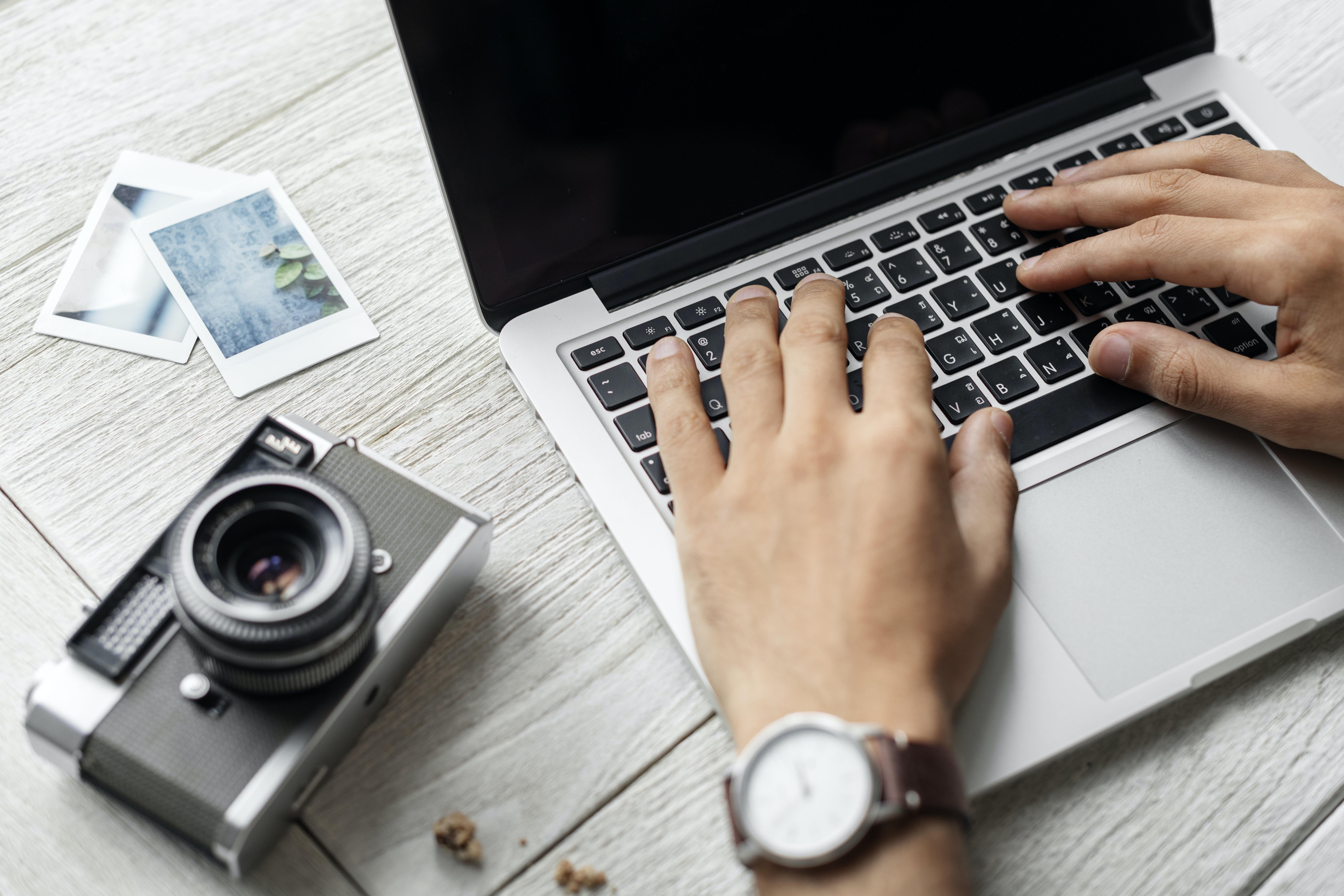 person using MacBook Pro beside film camera