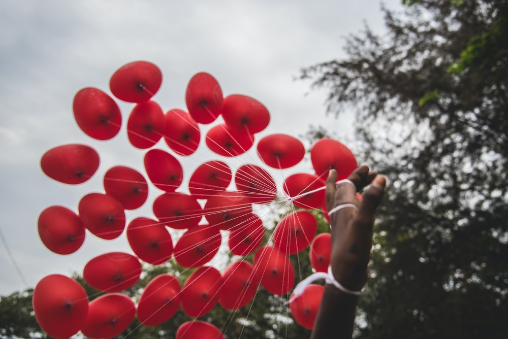 person hand holding red balloons