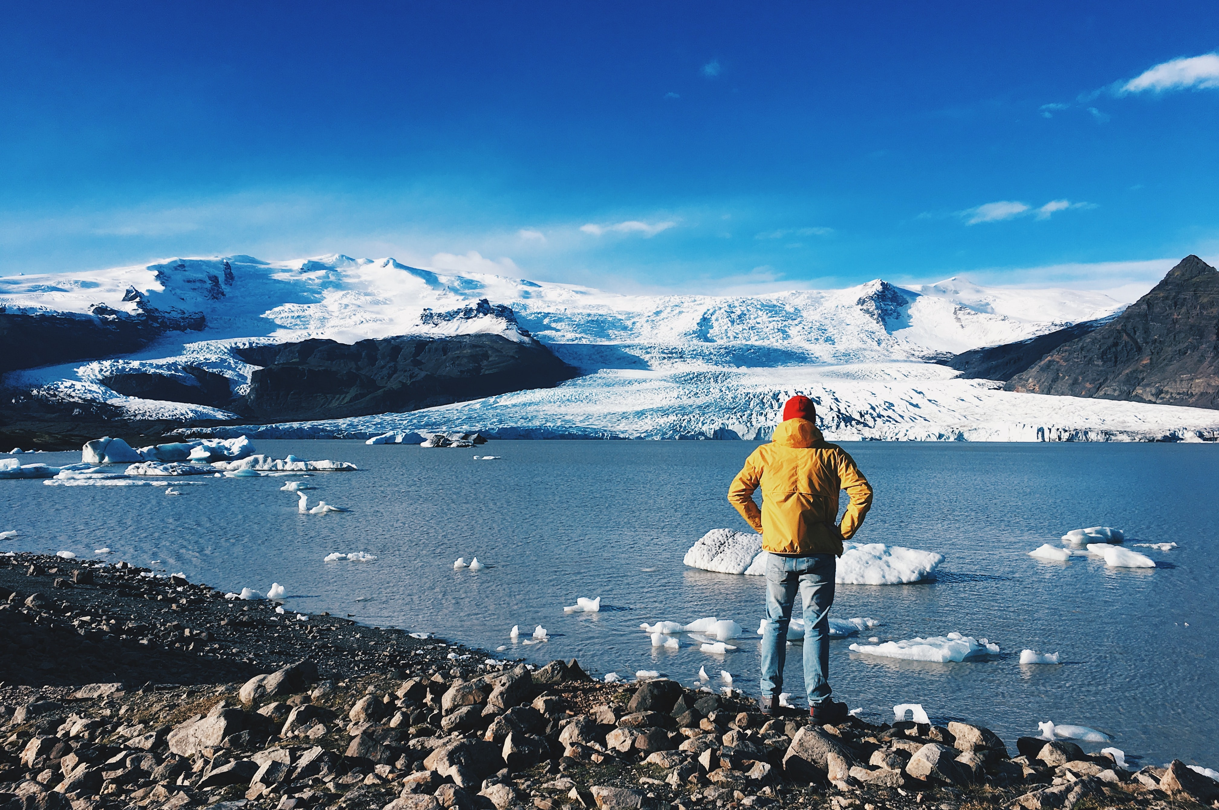 man standing in front of ice lake