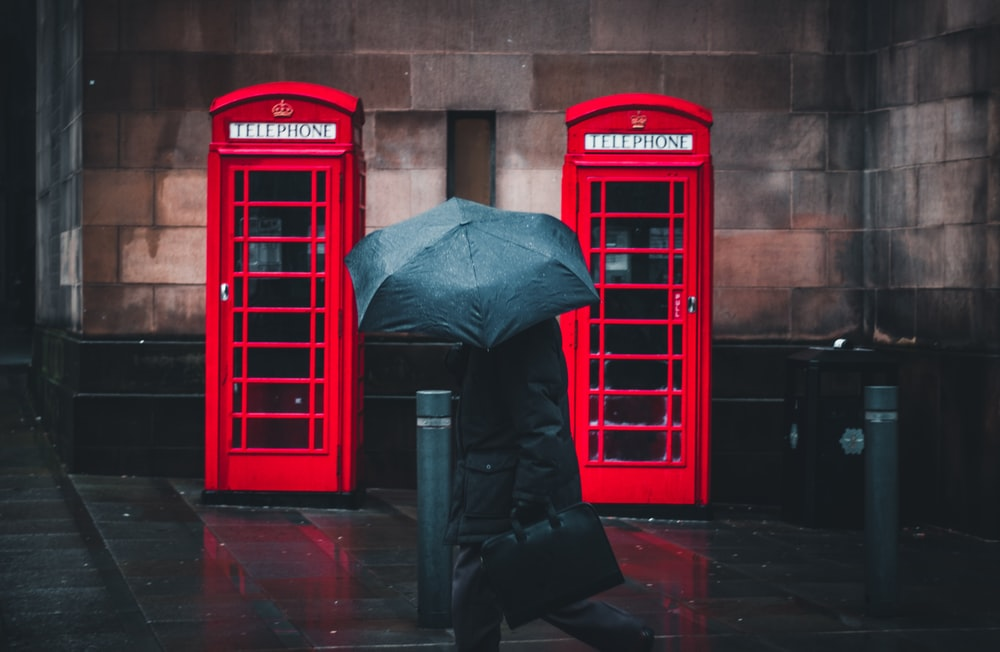 person under umbrella walking beside telephone booths