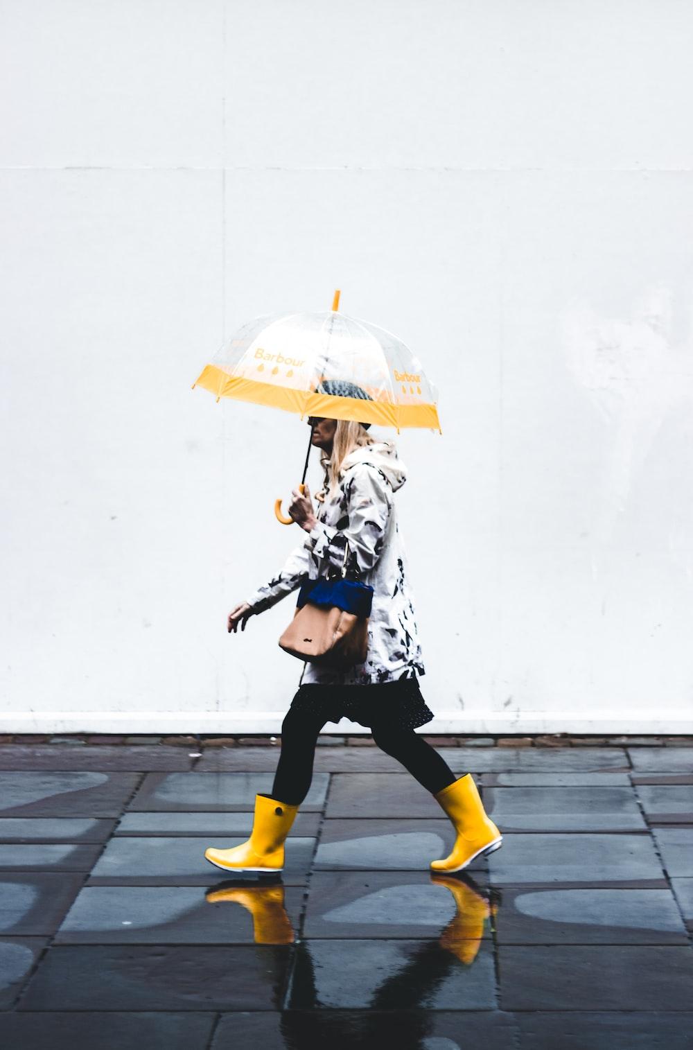 woman walking while holding opened yellow umbrella