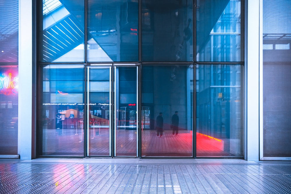 reflection of two men walking on glass building wall