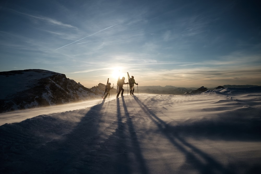 three people walking on snow-capped mountain during daytime