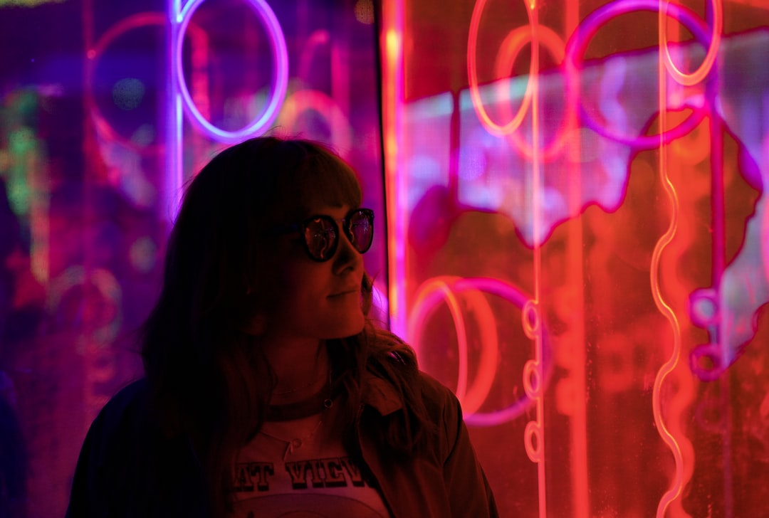 Woman by pink and red neon sign