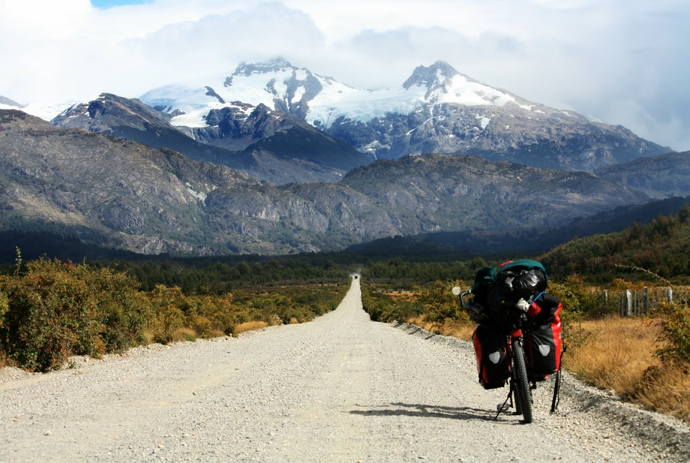 black motorcycle parked at road toward glacier mountain photo during daytime