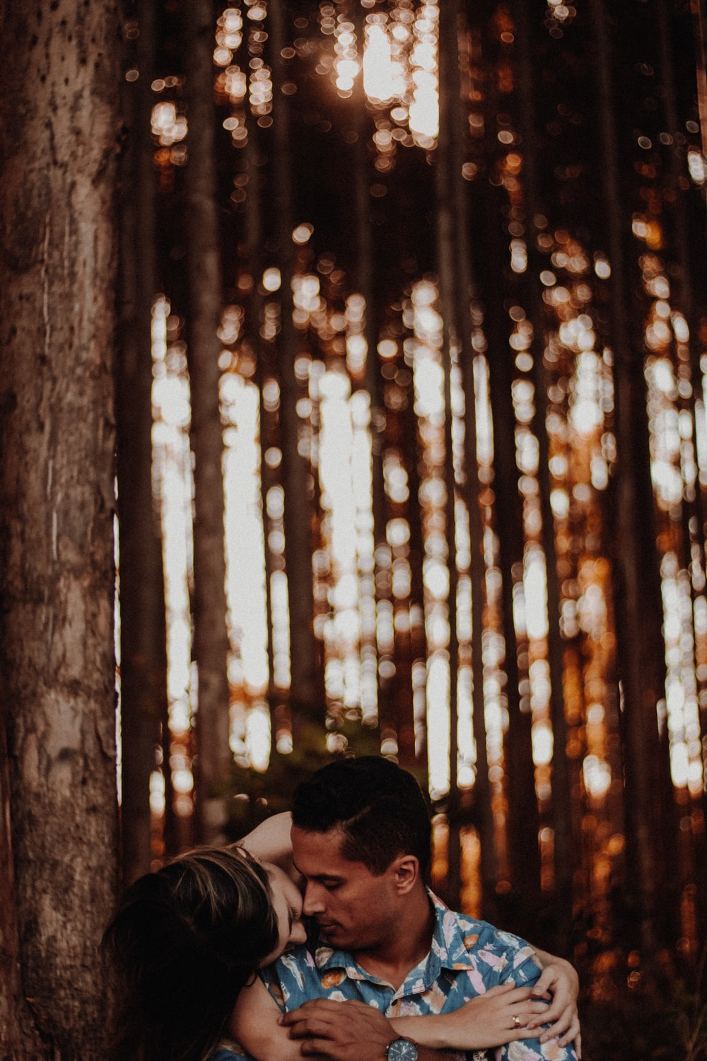 man and woman hugging near tall tree during daytime