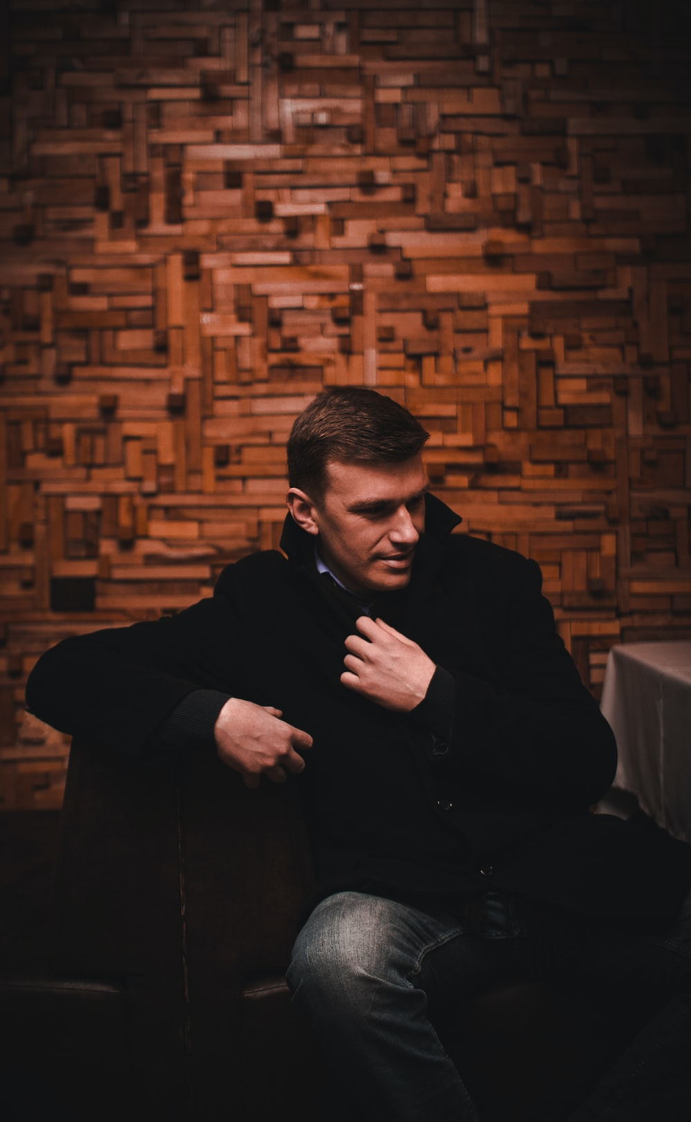man in black coat and blue denim jeans sitting near brown wall