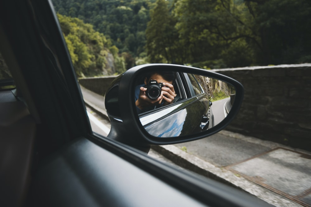 person taking picture on black car wing mirror