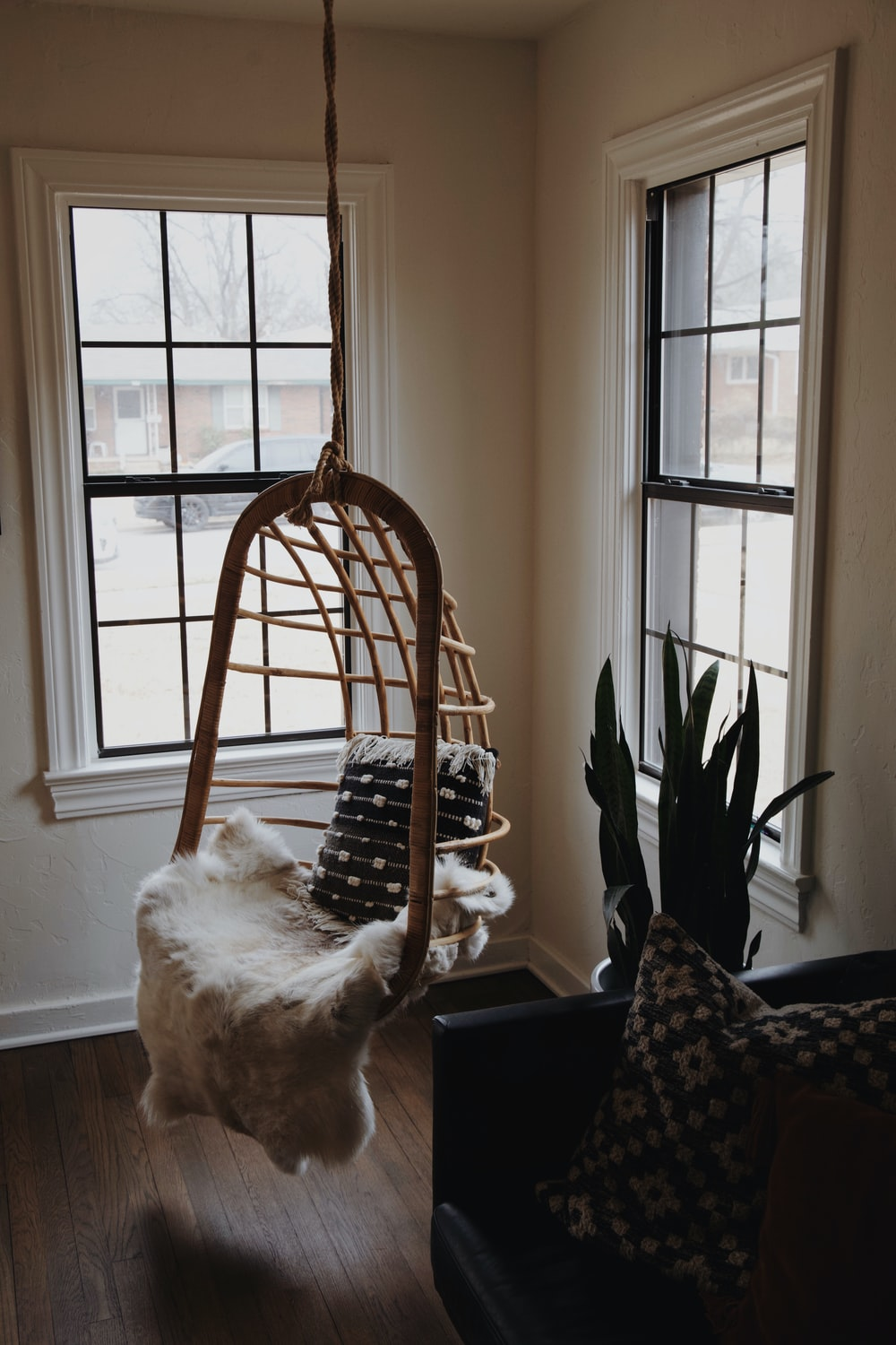 brown wooden hanging chair with white fleece blanket and gray throw pillow beside window during daytime
