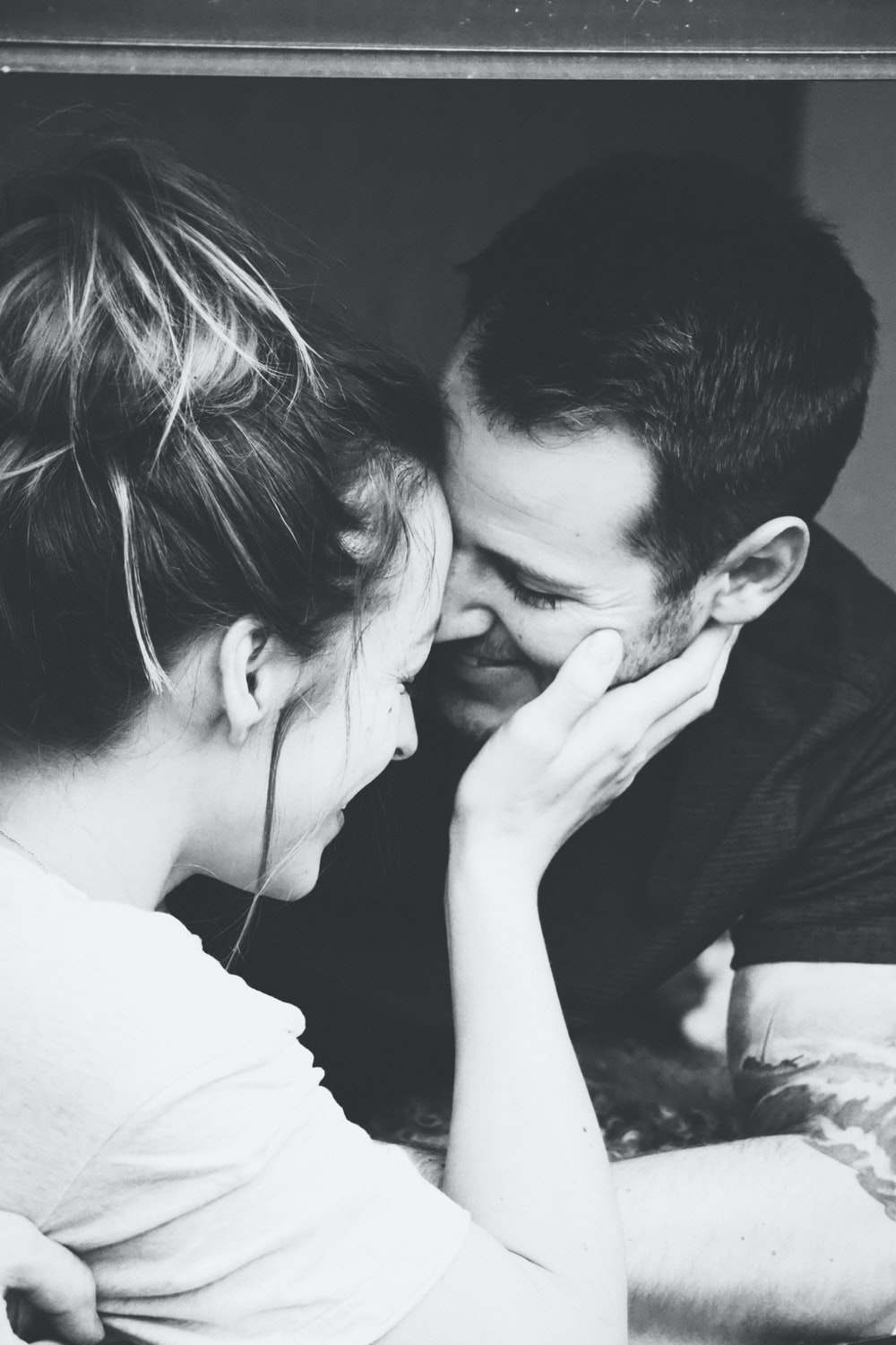 grayscale photography of woman holding man's face