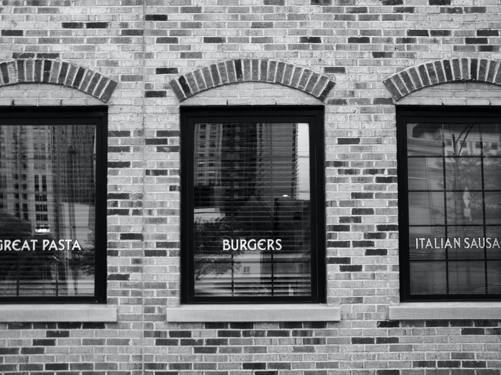 grayscale photography of building with glass windows