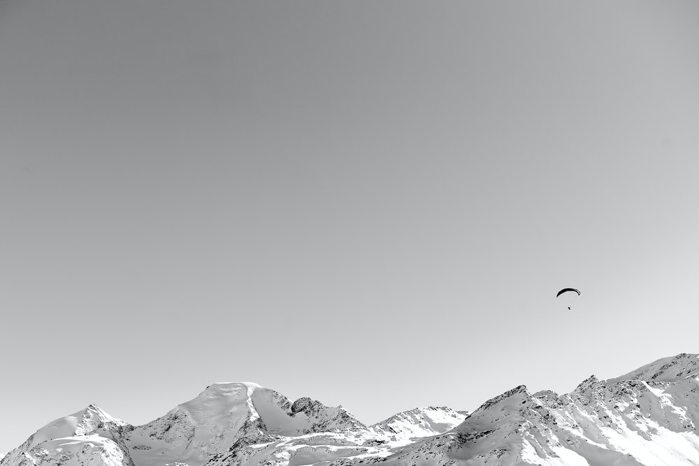 person riding parachute over snow covered mountain