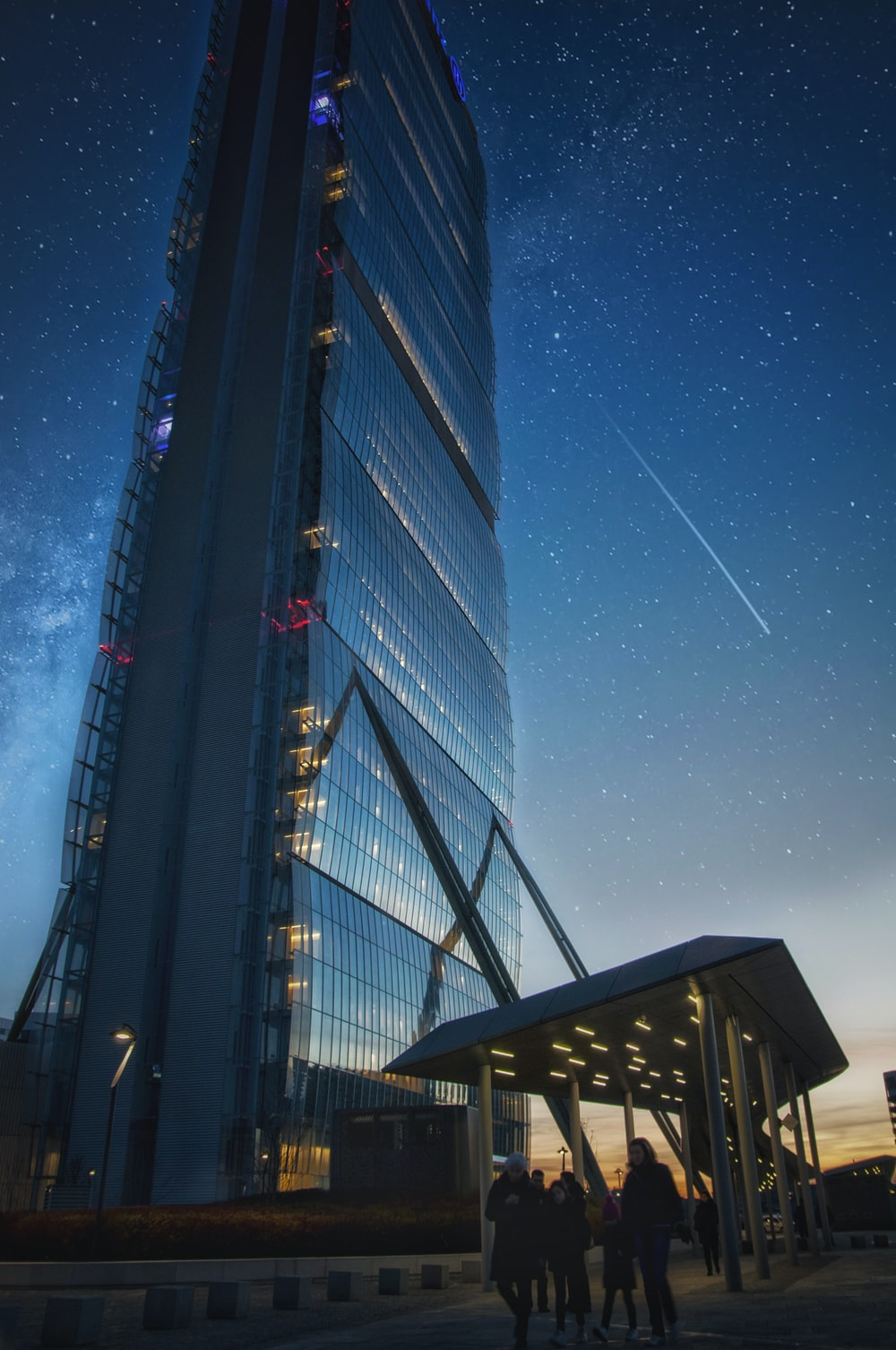 people walking near curtain wall high-rise building under starry sky