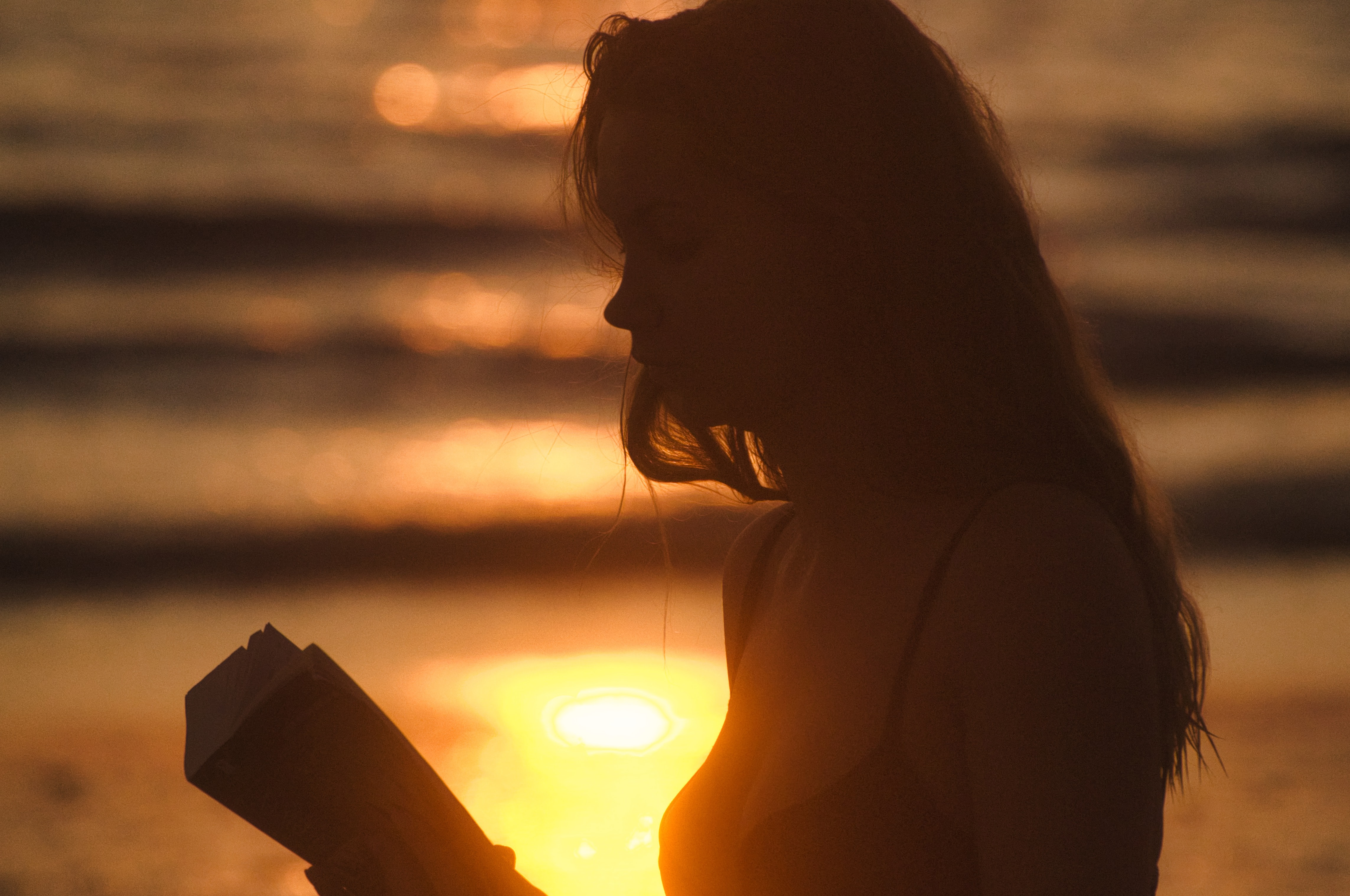 woman reading near body of water during golden hour