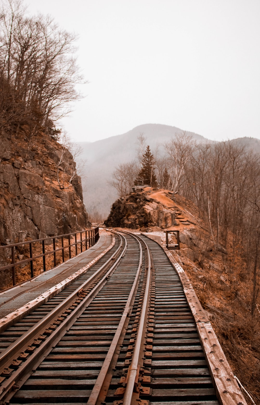 brown and gray train rails between rock hill and cliff