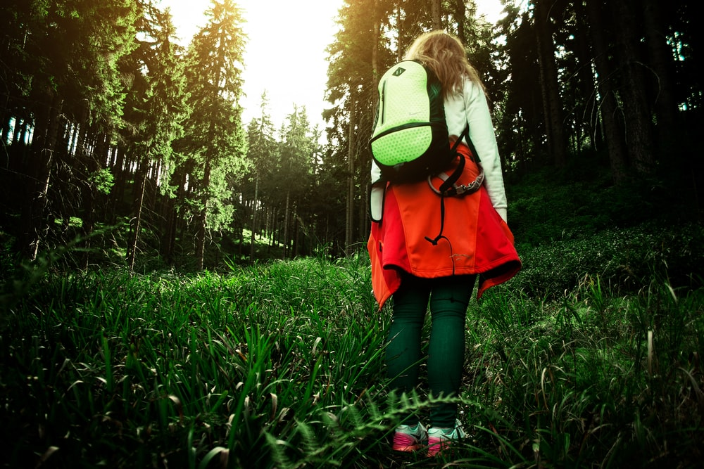 woman carrying green backpack walking in the grass filed