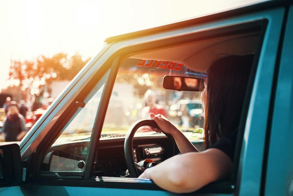 woman holding steering wheel sitting inside car