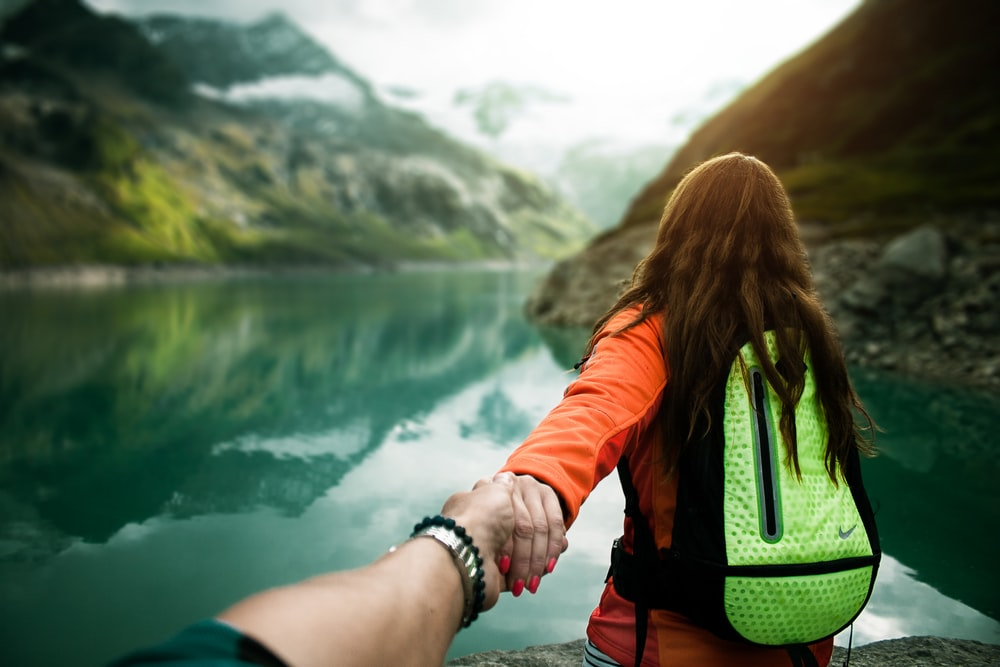 woman holding man's hand in front of water