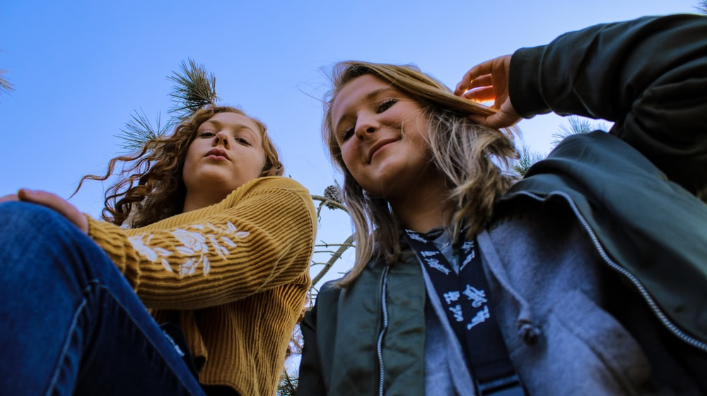 two women posing and looking down at the camera