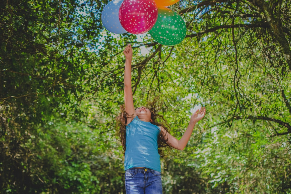 girl playing balloons under tree