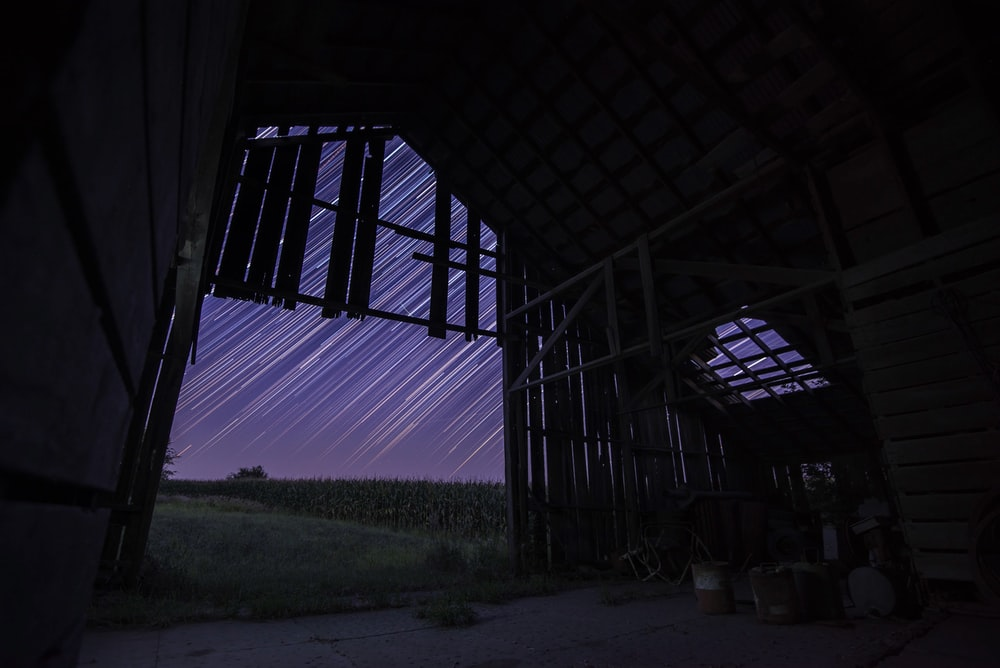 long exposure of stars above brown wooden house during nightime