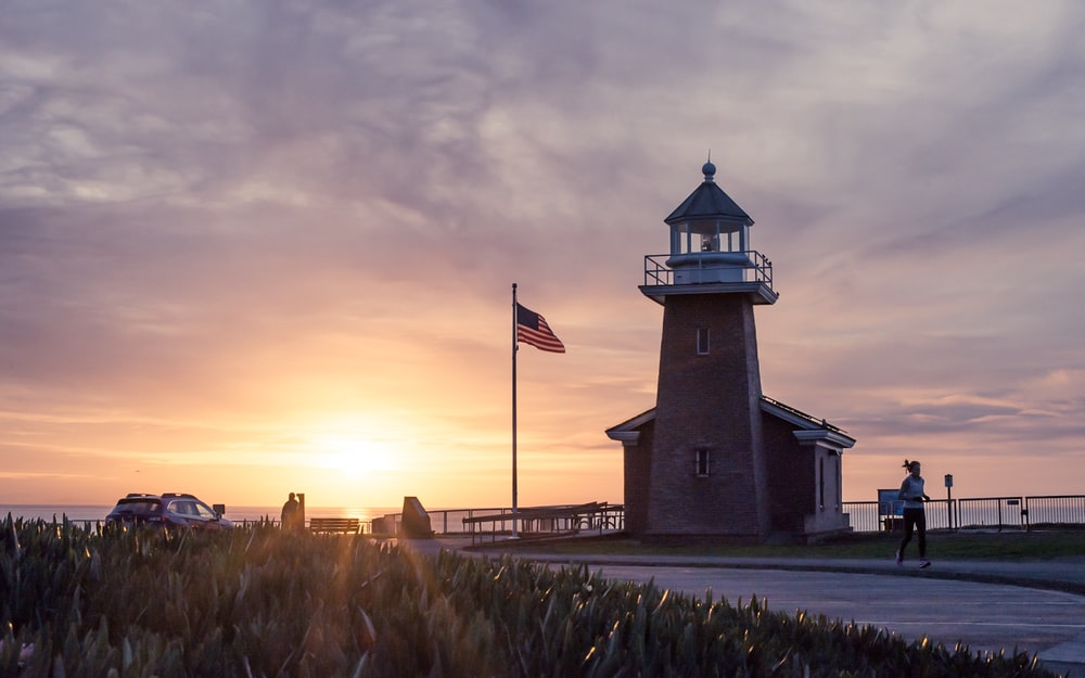 person jogging near lighthouse beside flagpole during sunset