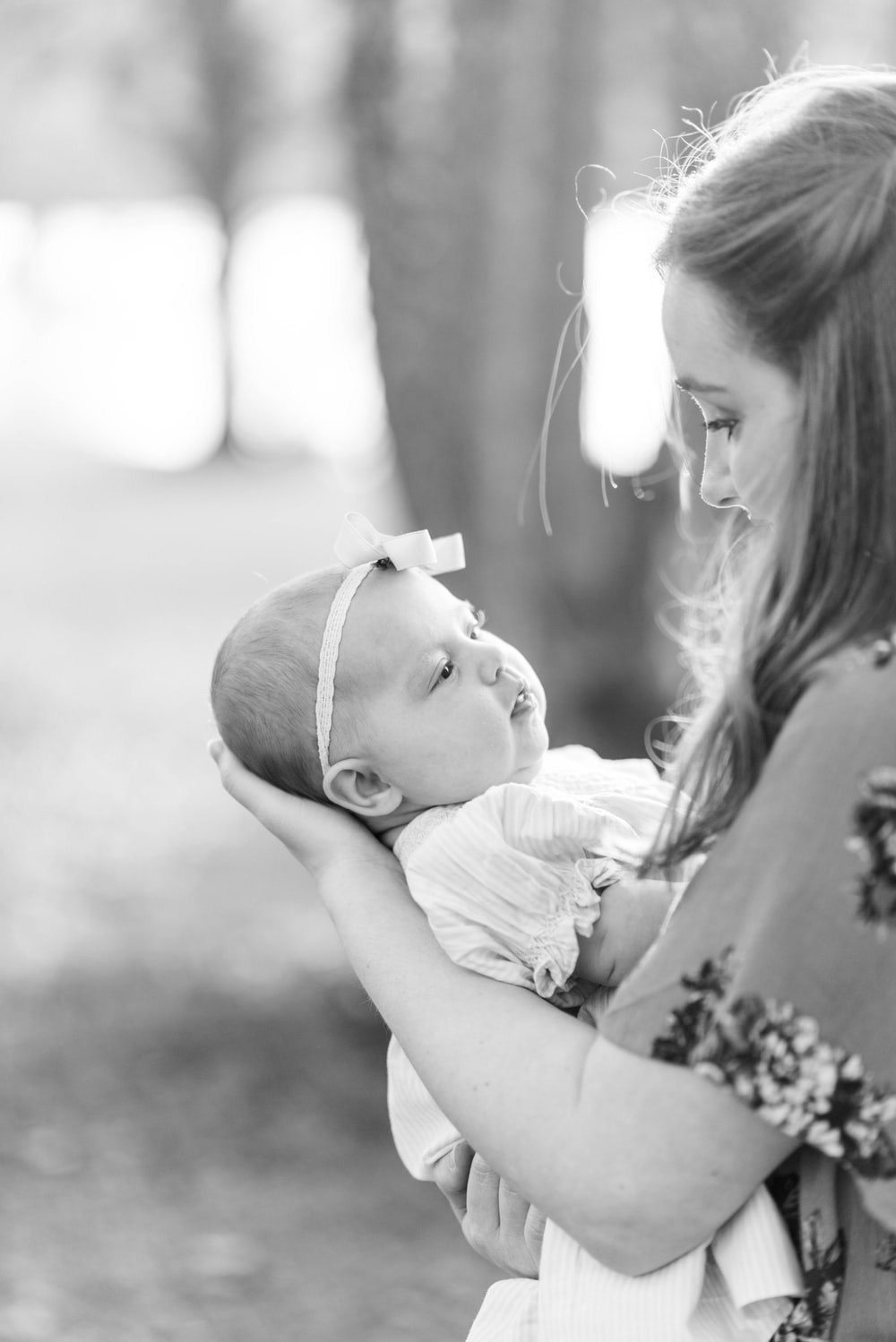 greyscale selective focus photo of woman carrying baby