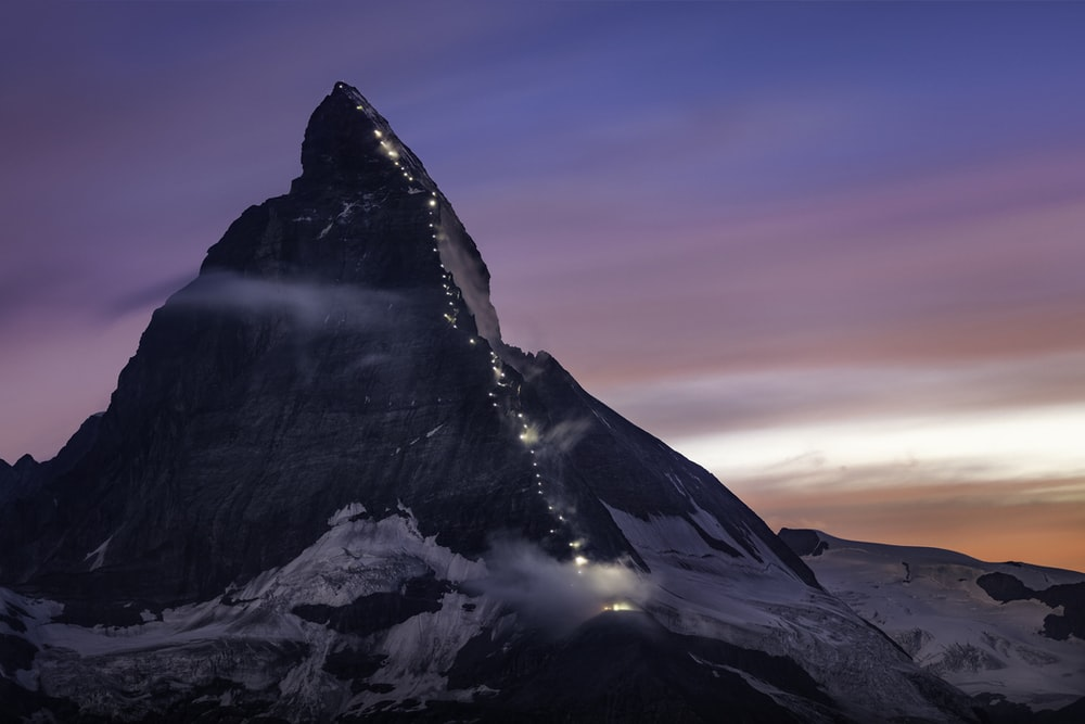 mountain covered with snow under orange and blue sky at daytime