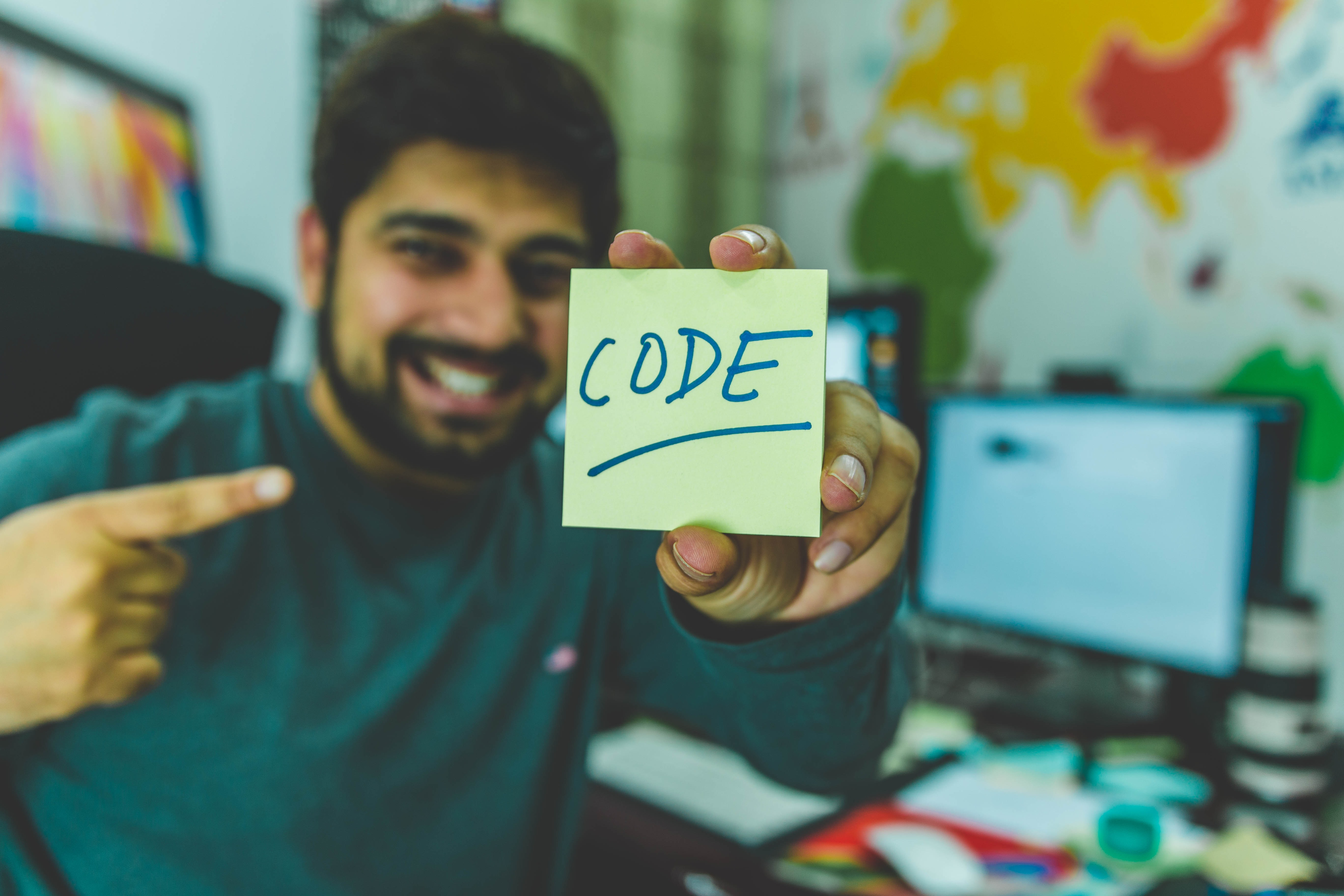 smiling man showing sticky note with code illustration