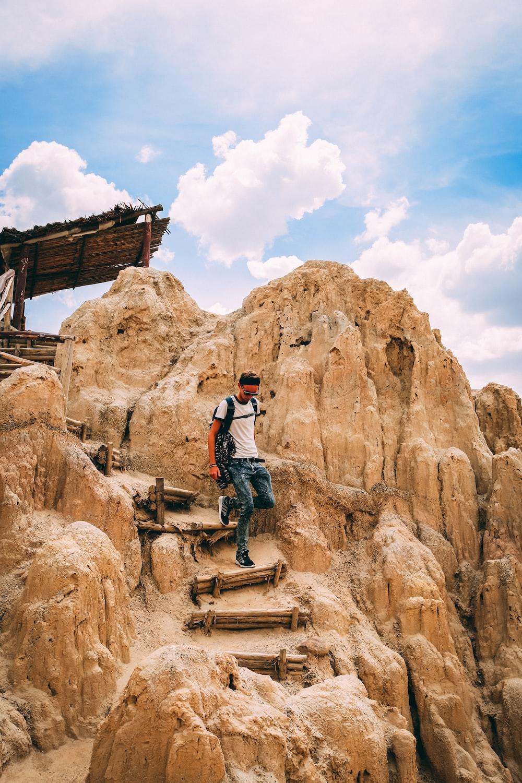 man walking down stairs of rock formation mountain during daytime