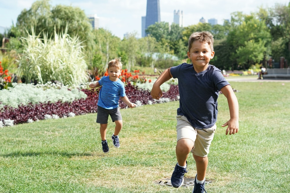 two boys walking on grasses during daytime