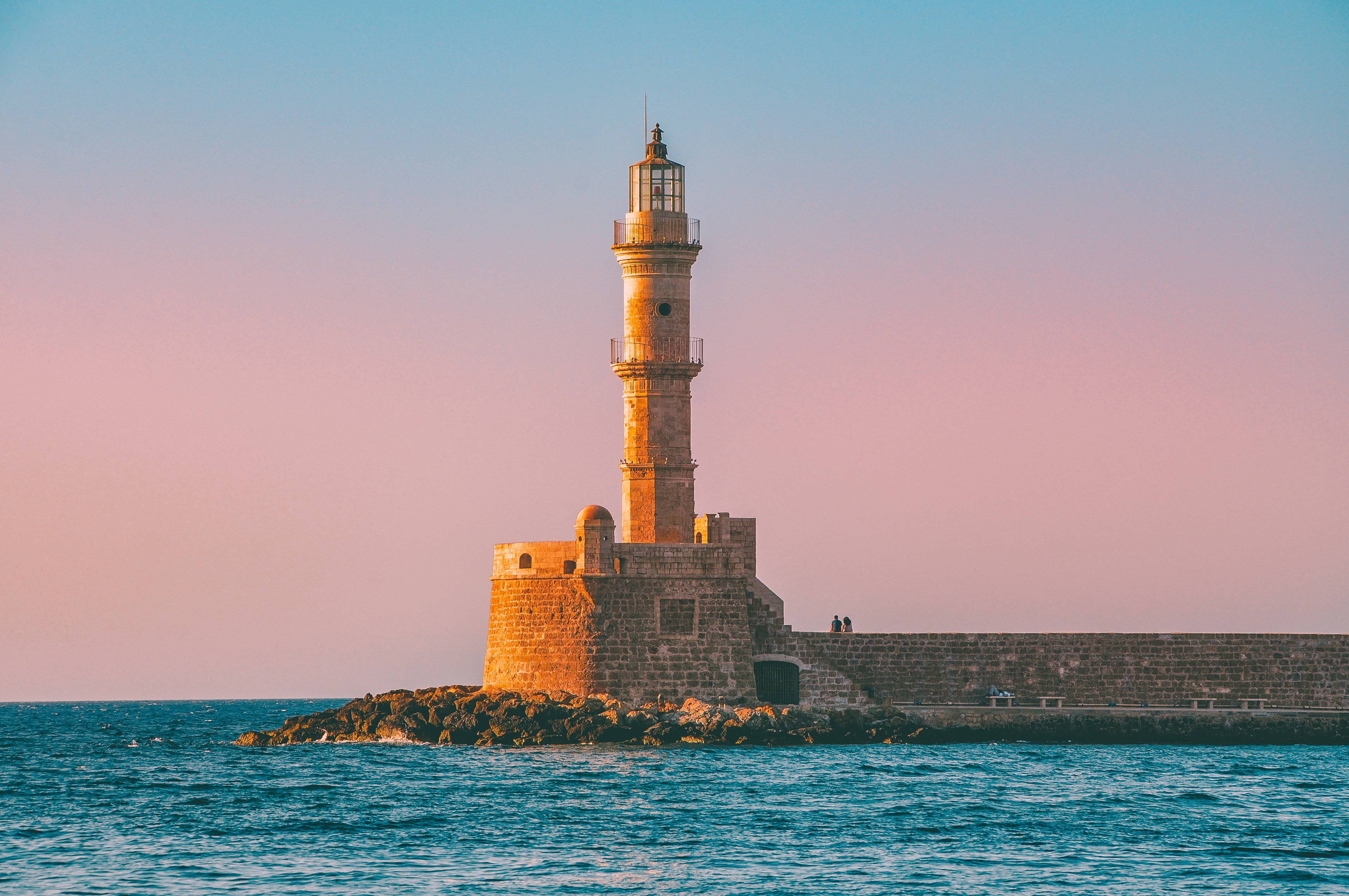lighthouse with body of water under blue sky during daytime