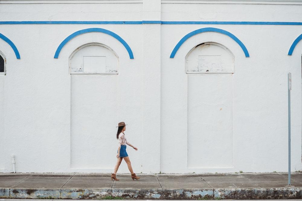 woman walking near white concrete building during daytime