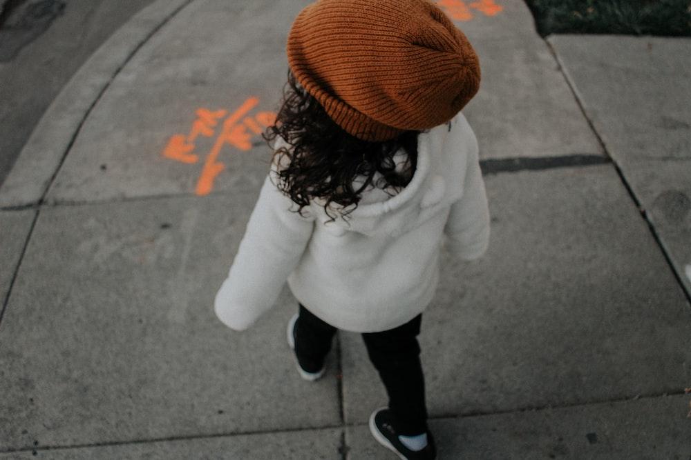 girl walking on side walk in street