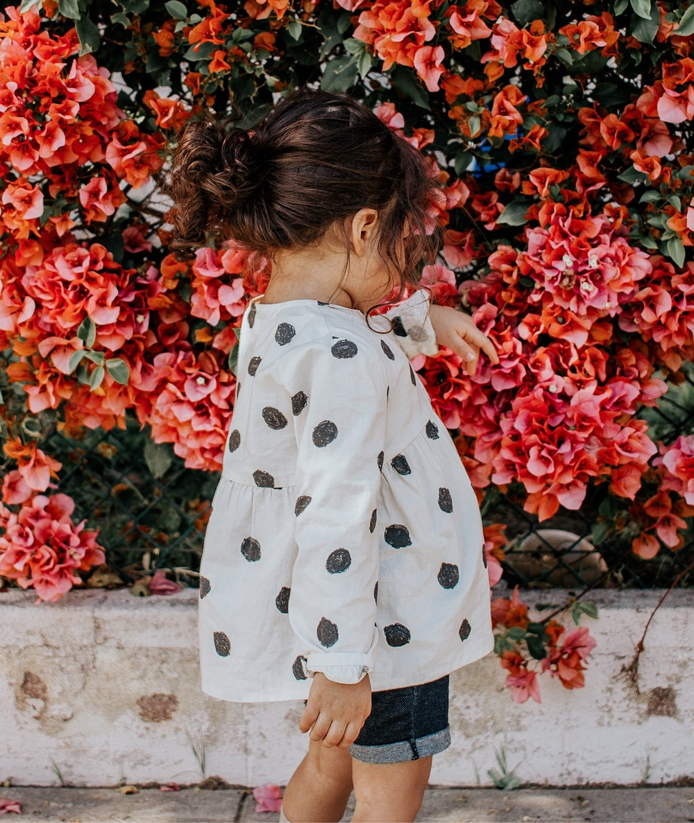 girl in black and white polka-dot long-sleeved blouse and blue shorts standing beside red petaled flowers during daytime