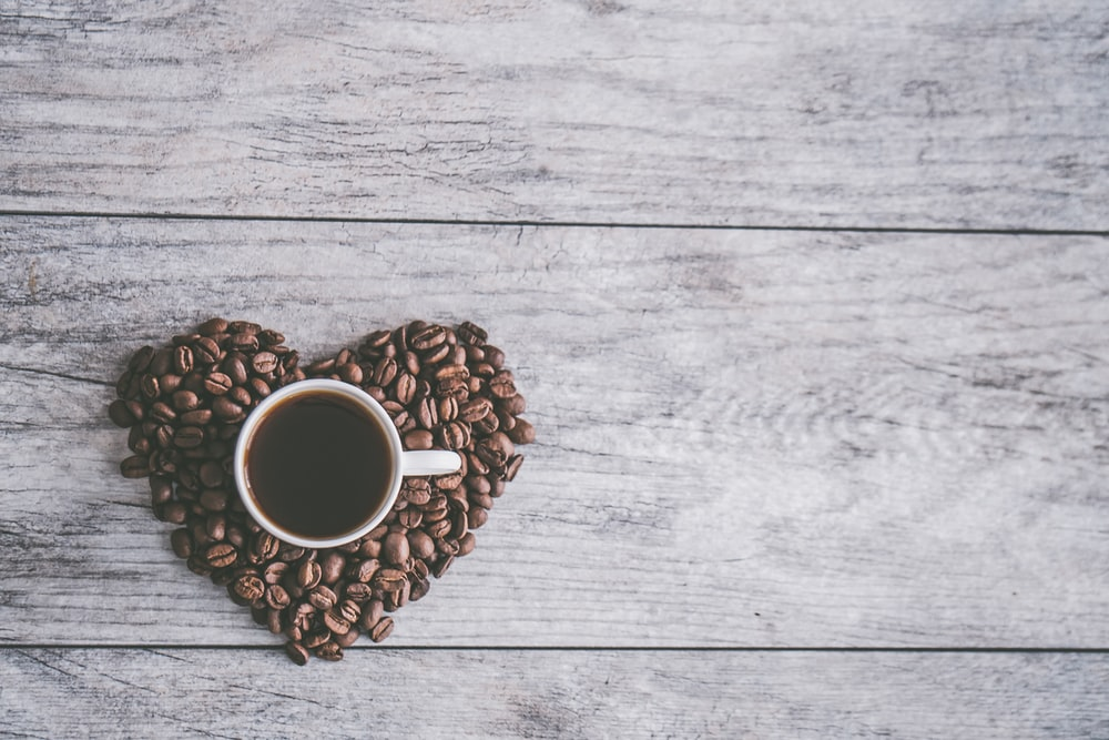 coffee filled white ceramic mug beside brown coffee beans on beige wooden surface