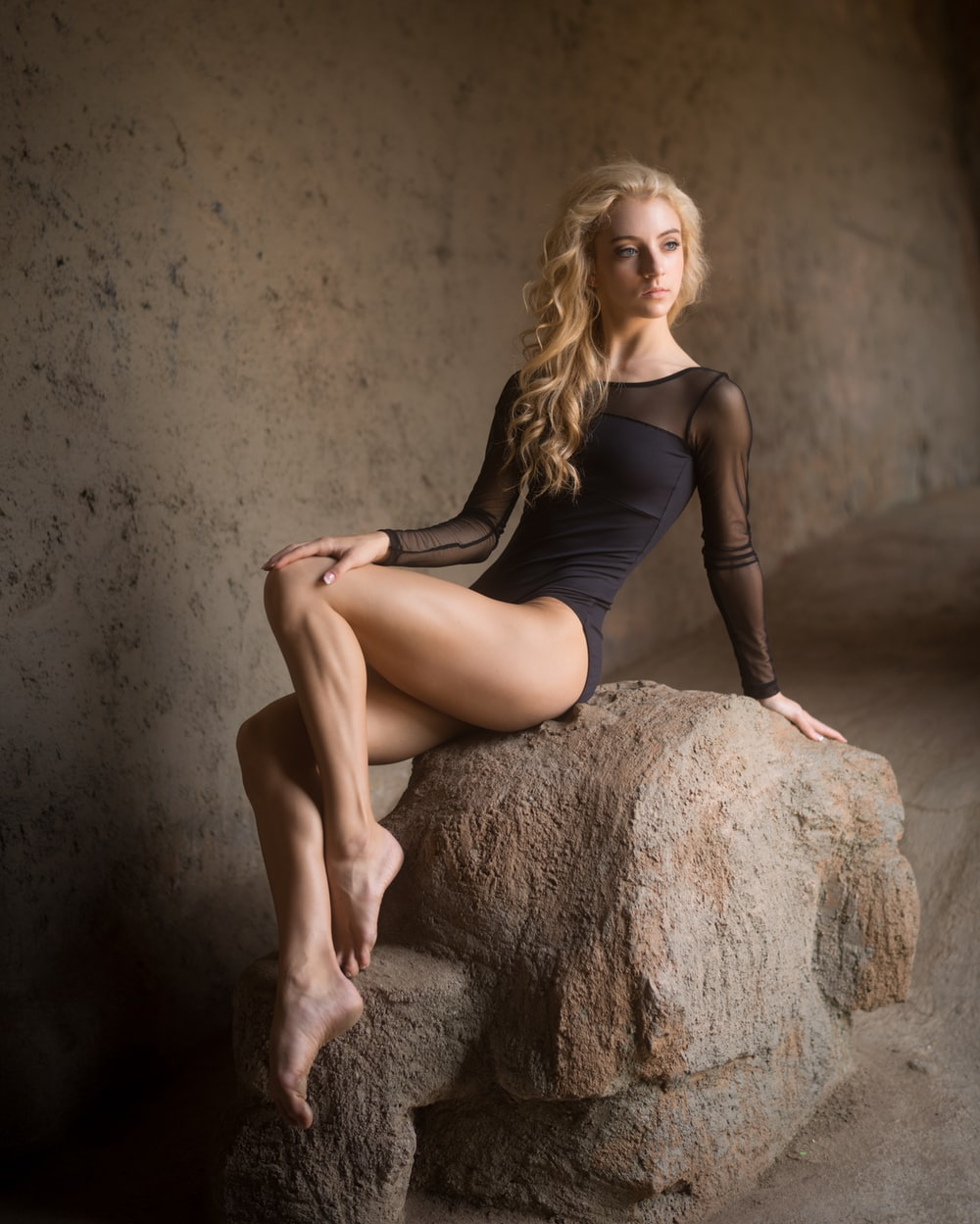 woman wearing body suit sitting on rock