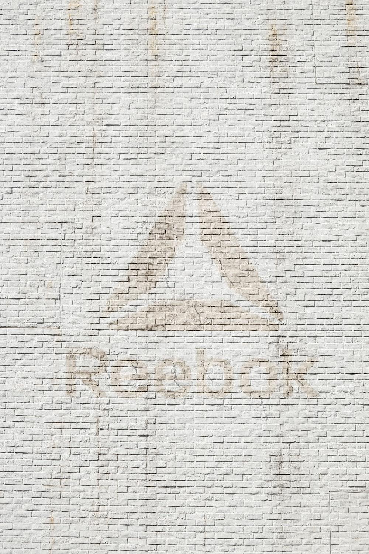 close-up photo of Reebok logo on wall