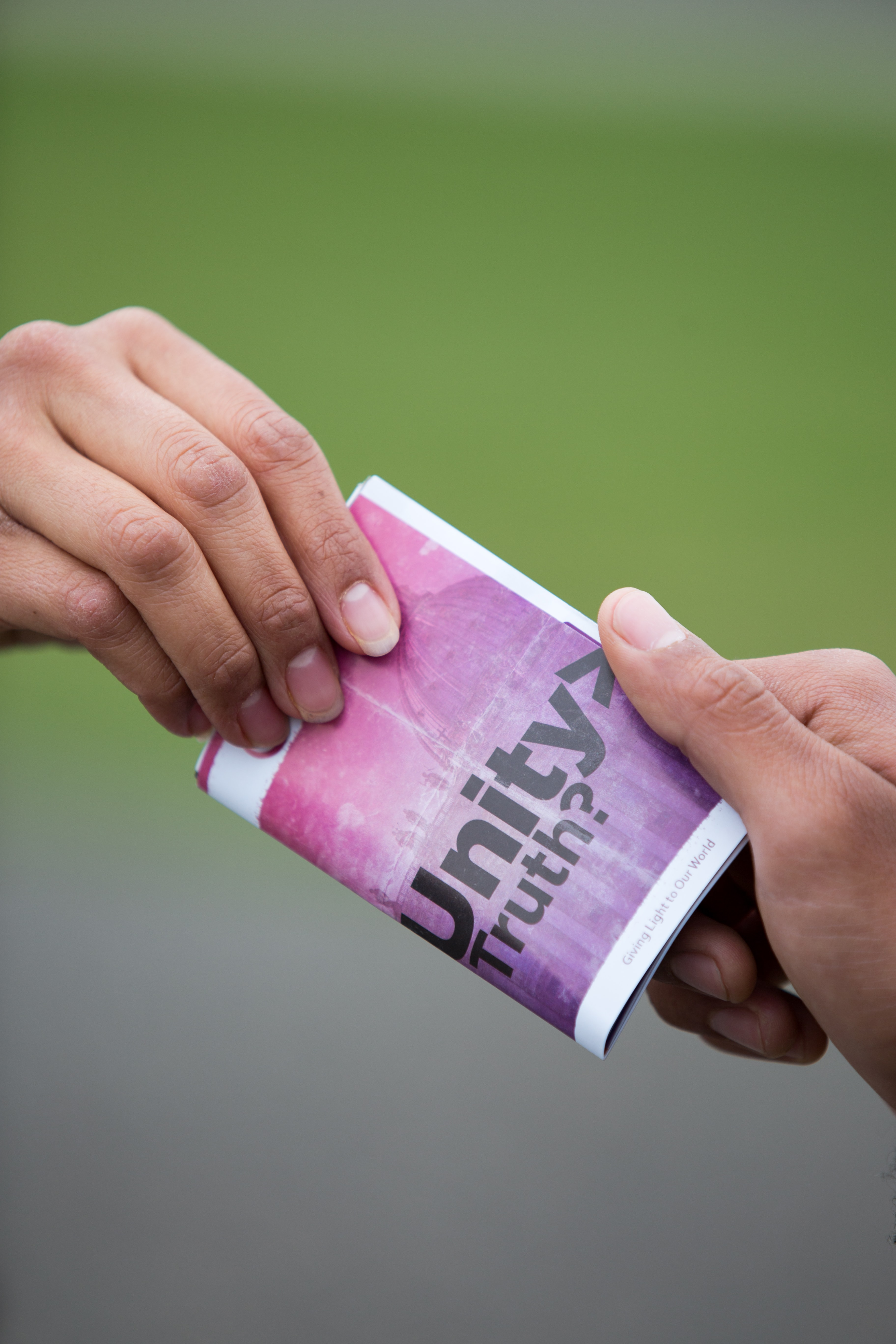selective focus photography of two persons holding purple and white Unity truth? booklet