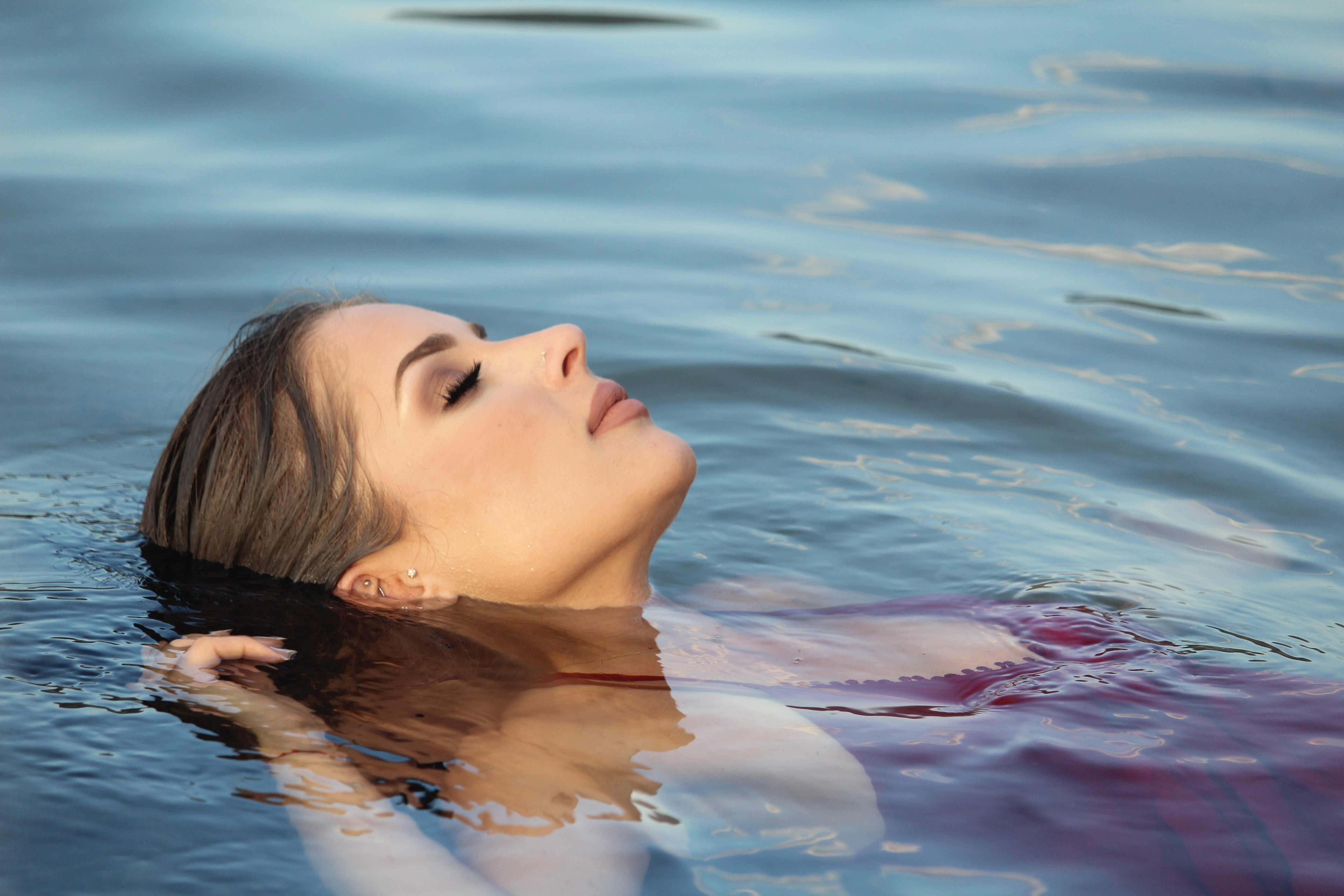 woman in maroon top floating on water during daytime