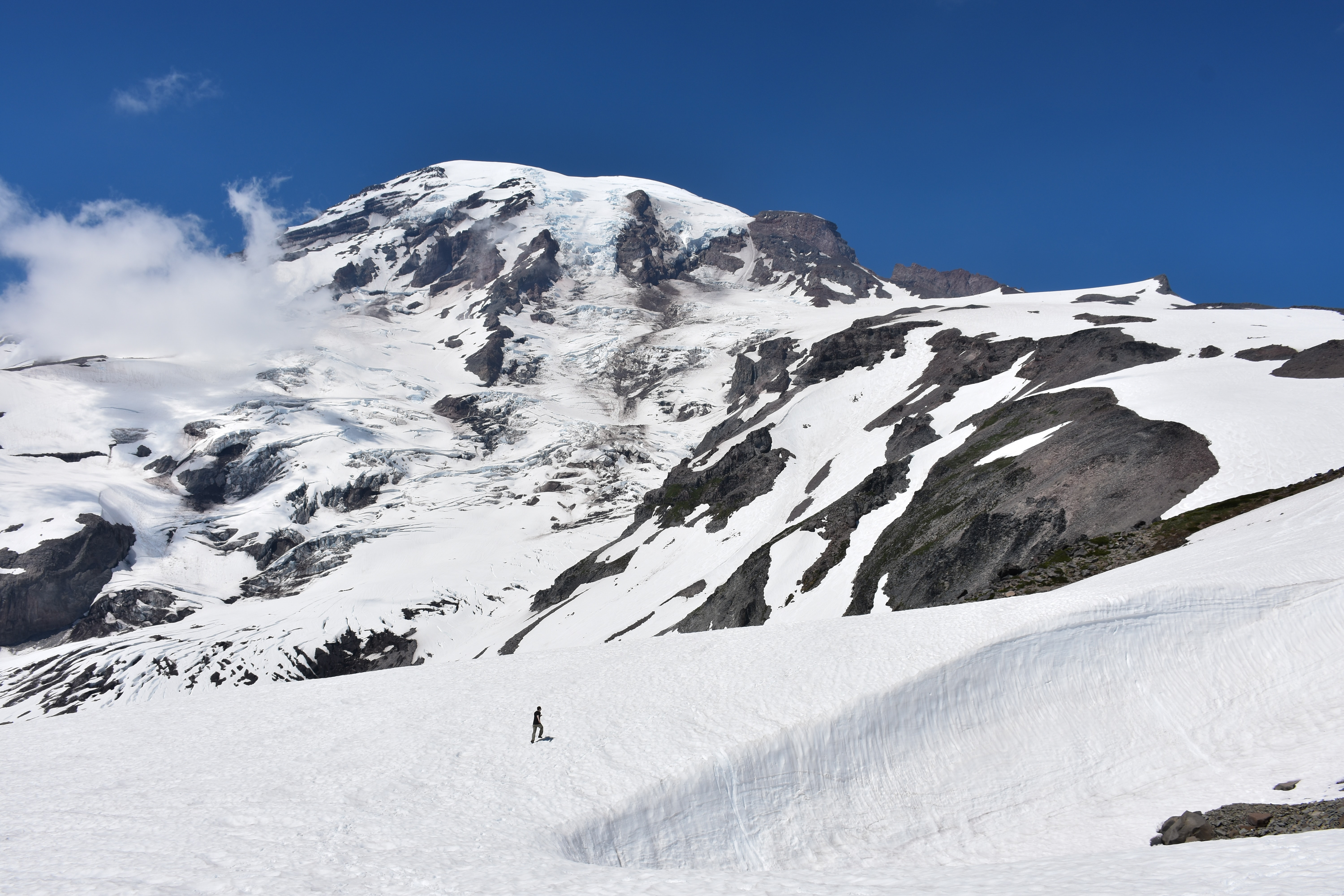 person walking on mountain covered by snow