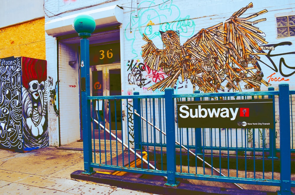 blue metal rail with Subway signage near building with graffiti art