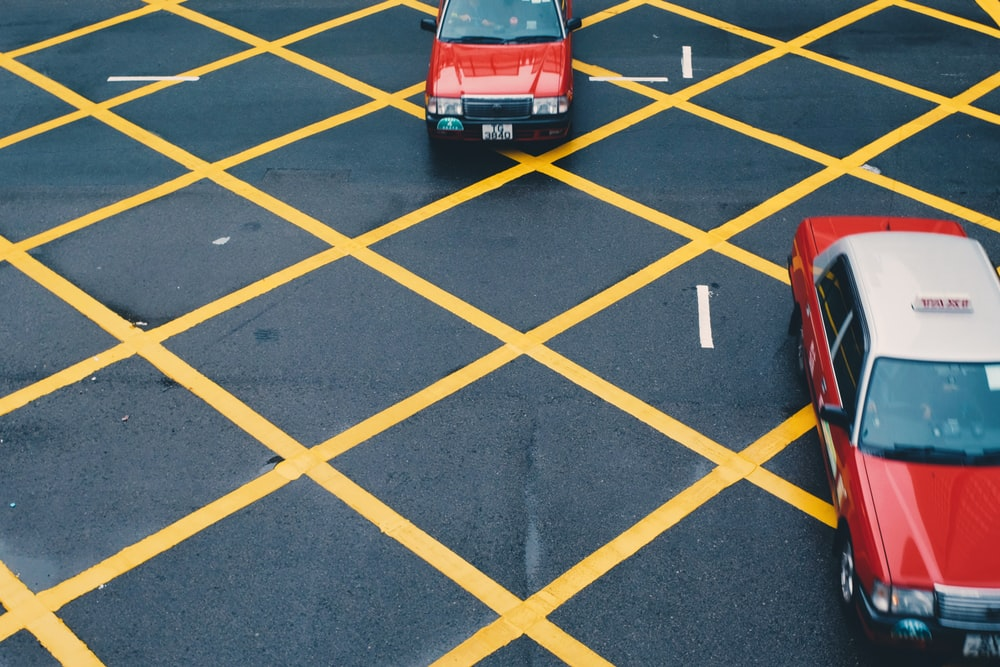two red vehicles on gray and yellow concrete road