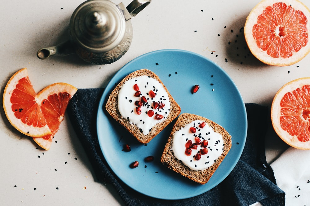 two baked breads with white mayonnaise and red fruits on top in round blue ceramic plate