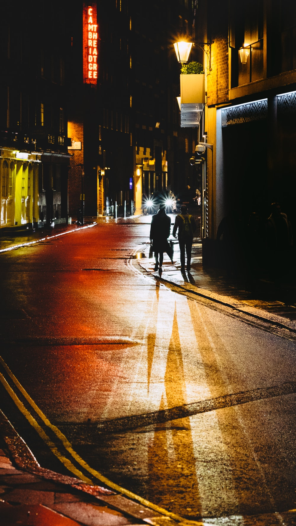 two people walking on street beside building during night time