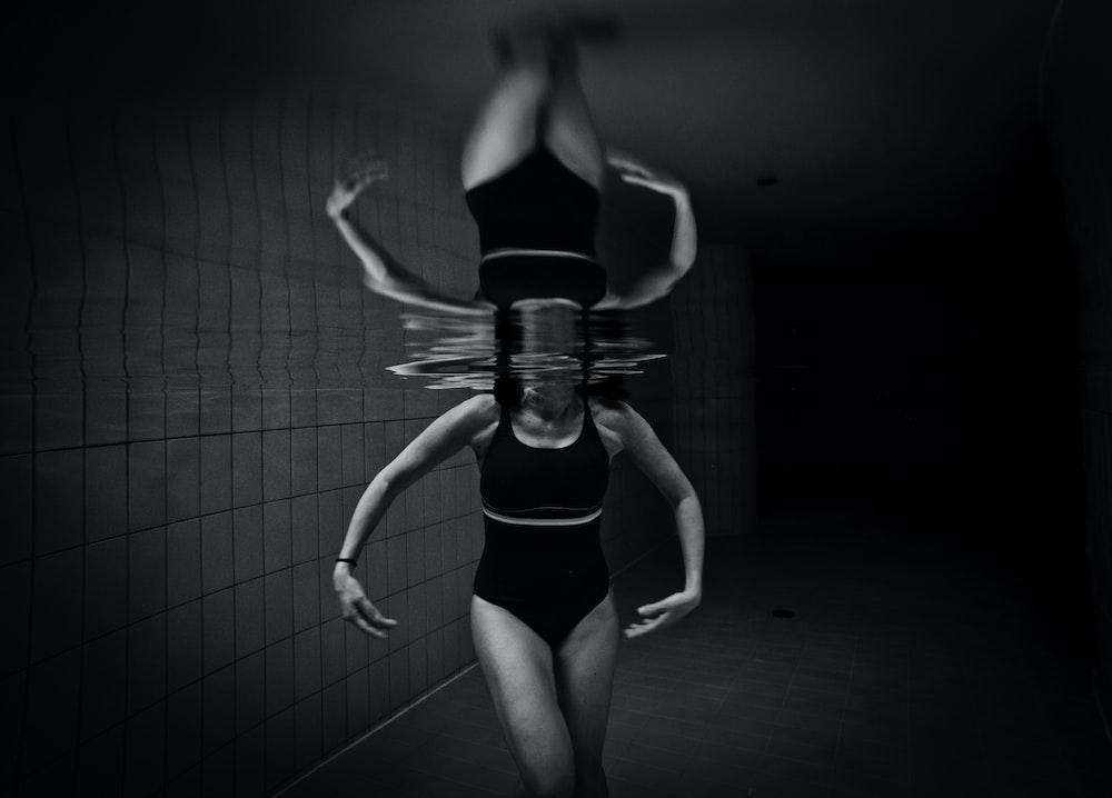 grayscale photo of woman wearing monokini on body of water
