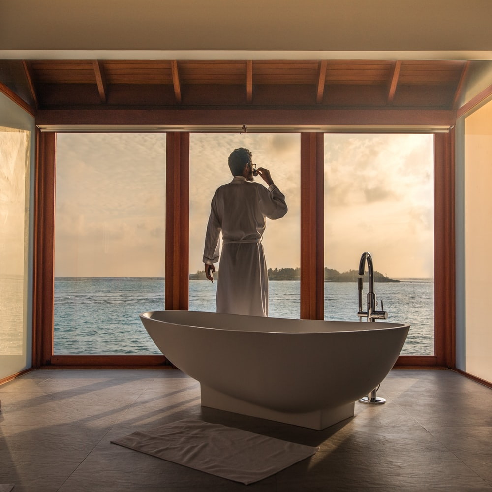 man standing in bathroom with bathtub next to body of water