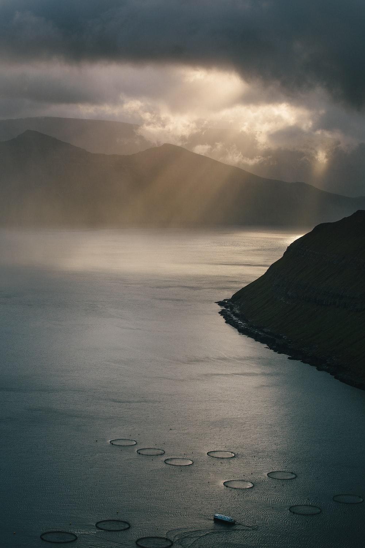 mountain near body of water under cloudy sky