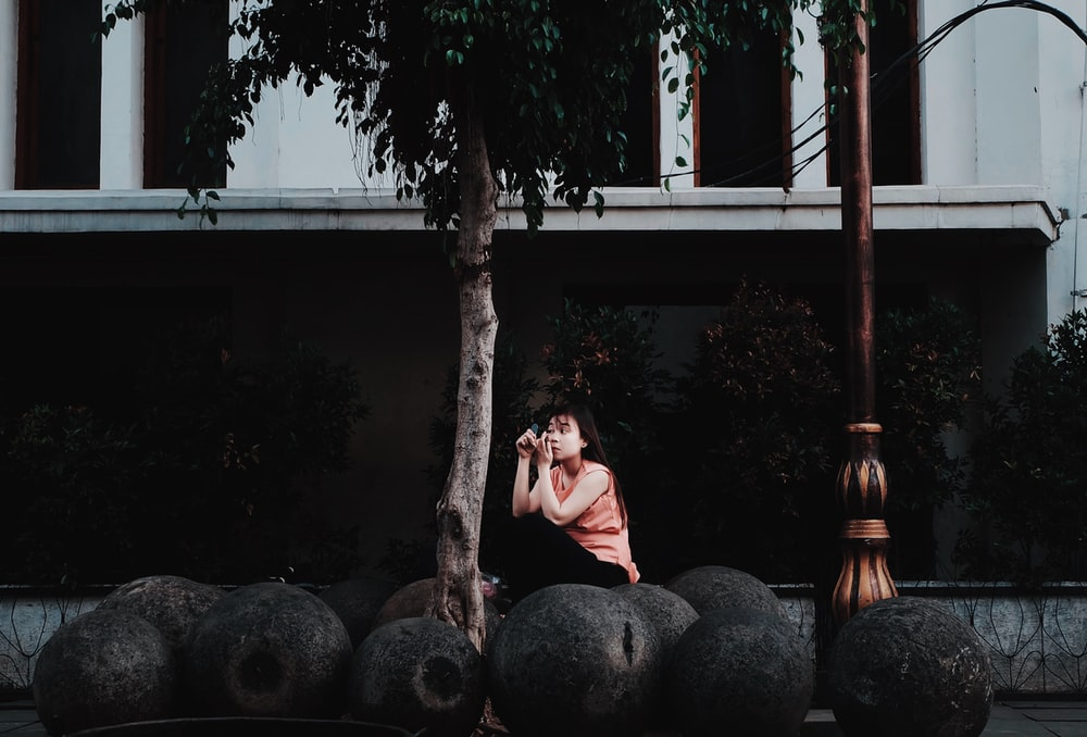 woman sitting on black stones
