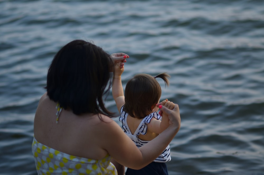 woman holding girl near body of water